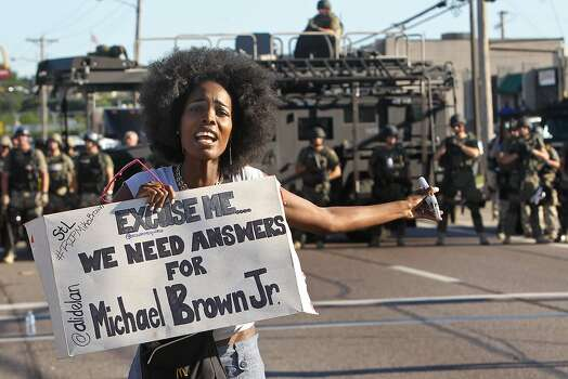 A protester shouts as she moves away from a line of riot police in Ferguson, Mo. on Wednesday, Aug. 13, 2014. On Saturday, Aug. 9, 2014, a white police officer fatally shot Michael Brown, an unarmed black teenager, in the St. Louis suburb.  Photo: J.B. Forbes, Associated Press
