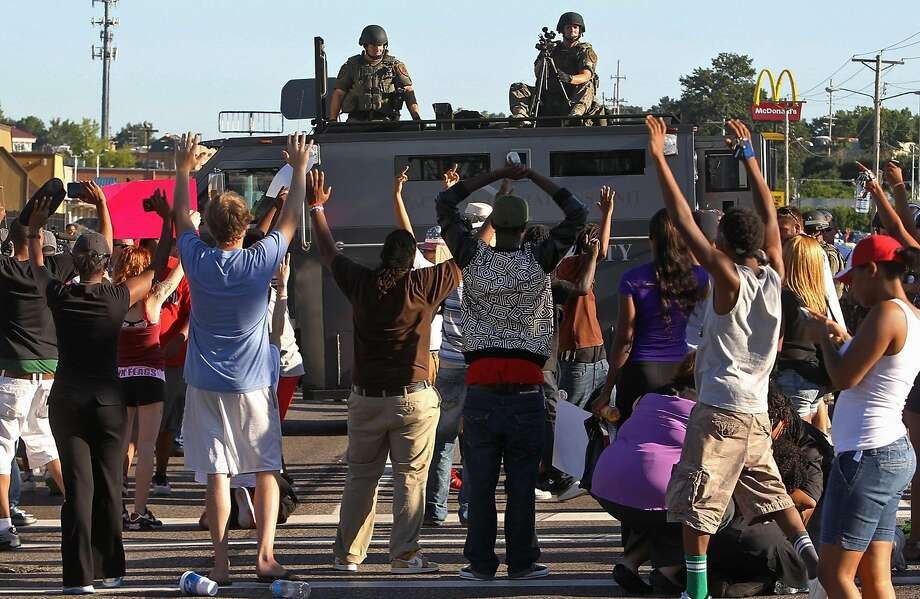 Protesters raise their hands in front of police atop an armored vehicle in Ferguson, Mo. on Wednesday, Aug. 13, 2014. On Saturday, Aug. 9, 2014, a white police officer fatally shot Michael Brown, an unarmed black teenager, in the St. Louis suburb. Photo: J.B. Forbes, Associated Press