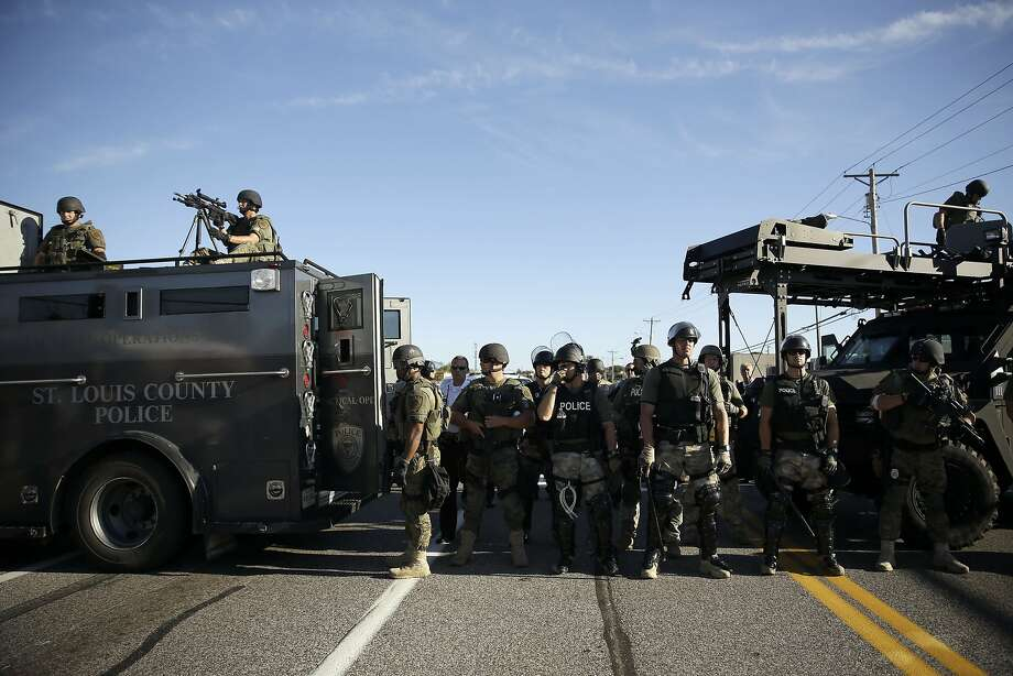 Police in riot gear watch protesters in Ferguson, Mo. on Wednesday, Aug. 13, 2014. On Saturday, Aug. 9, 2014, a white police officer fatally shot Michael Brown, an unarmed black teenager, in the St. Louis suburb.  Photo: Jeff Roberson, Associated Press