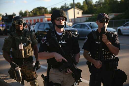 Police take up position to control demonstrators who were protesting the killing of teenager Michael Brown on August 12, 2014 in Ferguson, Missouri. Brown was shot and killed by a police officer on Saturday in the St. Louis suburb of Ferguson. Ferguson has experienced two days of violent protests since the killing but, tonight's protest was peaceful.  Photo: Scott Olson, Getty Images