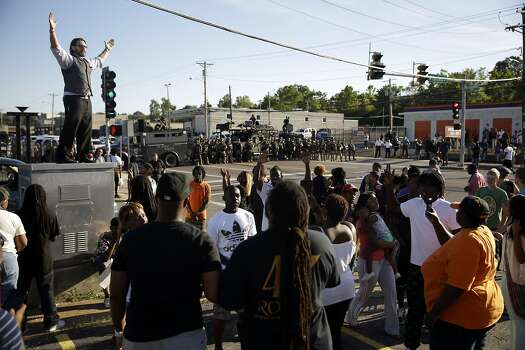 A man tries to calm a group of protesters as police stand in the distance in Ferguson, Mo. on Wednesday, Aug. 13, 2014. On Saturday, Aug. 9, 2014, a white police officer fatally shot Michael Brown, an unarmed black teenager.  Photo: Jeff Roberson, Associated Press