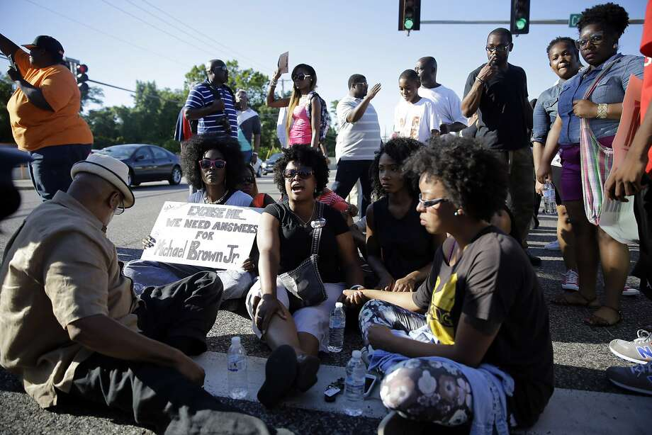 A small group of protesters block traffic by sitting in the street before police in riot gear arrived in Ferguson, Mo. on Wednesday, Aug. 13, 2014. On Saturday, Aug. 9, 2014, a white police officer fatally shot Michael Brown, an unarmed black teenager in the St. Louis suburb. Photo: Jeff Roberson, Associated Press