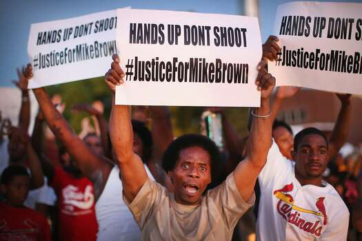 Demonstrators protest the killing of teenager Michael Brown outside Greater St. Marks Family Church while Browns family along with civil rights leader Rev. Al Sharpton and a capacity crowd of guests met inside to discuss the killing on August 12, 2014 in St Louis, Missouri. Brown was shot and killed by a police officer on Saturday in the nearby suburb of Ferguson. Ferguson has experienced two days of violent protests since the killing but, tonight the town remained mostly peaceful.  Photo: Scott Olson, Getty Images