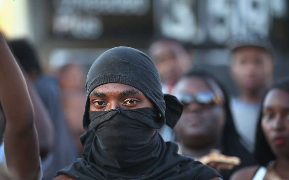 Demonstrators protest the killing of teenager Michael Brown on August 12, 2014 in Ferguson, Missouri. Brown was shot and killed by a police officer on Saturday in the St. Louis suburb of Ferguson. Ferguson has experienced two days of violent protests since the killing but, tonight's protest was peaceful.  Photo: Scott Olson, Getty Images