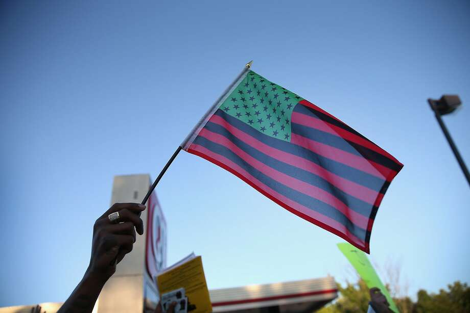 Demonstrators hold up an African American Flag during a protest the killing of teenager Michael Brown on August 12, 2014 in Ferguson, Missouri. Brown was shot and killed by a police officer on Saturday in the St. Louis suburb of Ferguson. Ferguson has experienced two days of violent protests since the killing but, tonight's protest was peaceful.  Photo: Scott Olson, Getty Images