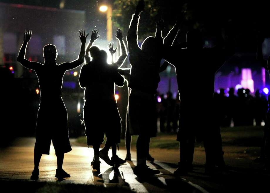 People raise their hands in the middle of the street as police wearing riot gear move toward their position trying to get them to disperse Monday, Aug. 11, 2014, in Ferguson, Mo. The FBI opened an investigation Monday into the death of 18-year-old Michael Brown, who police said was shot multiple times Saturday after being confronted by an officer in Ferguson. Authorities in Ferguson used tear gas and rubber bullets to try to disperse a large crowd Monday night that had gathered at the site of a burned-out convenience store damaged a night earlier, when many businesses in the area were looted. (AP Photo/Jeff Roberson) Photo: Jeff Roberson / Associated Press / AP