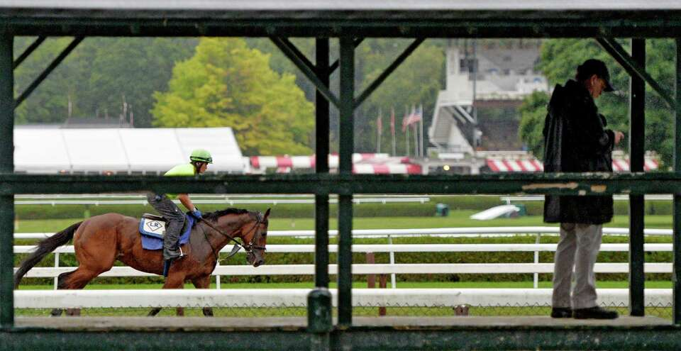 A trainer checks his phone as horses continue to work out in the heavy rain  Wednesday morning, Aug.