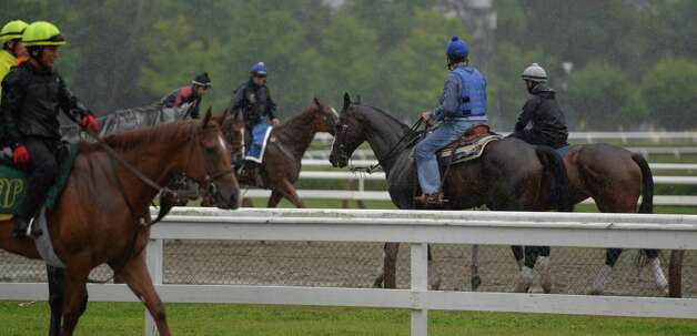 In spite of heavy rainfall horses continue to work out  Wednesday morning, Aug. 13, 2014, at  Saratoga Race Course in Saratoga Springs, N.Y.  (Skip Dickstein/Times Union) Photo: SKIP DICKSTEIN