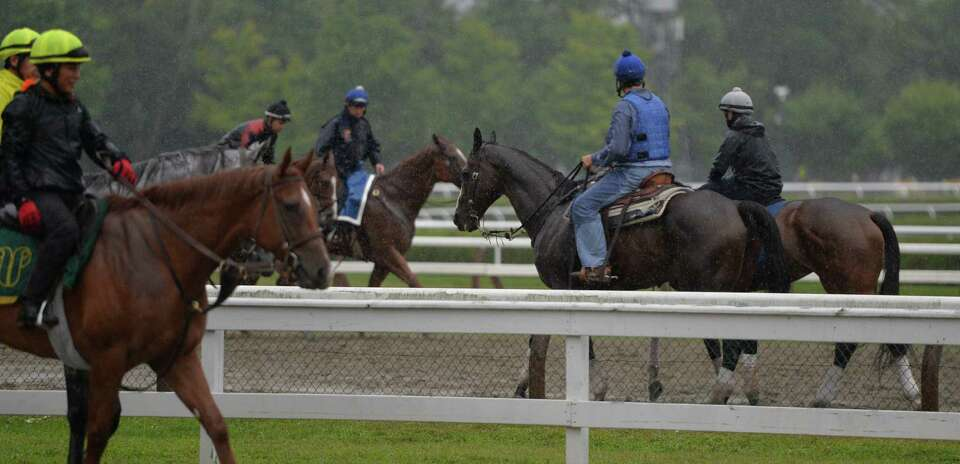 In spite of heavy rainfall horses continue to work out  Wednesday morning, Aug. 13, 2014, at  Sarato