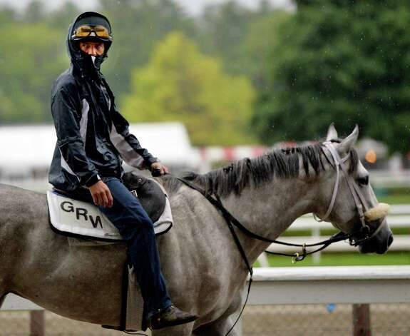 An exercise rider for trainer George Weaver protects himself from the rain Wednesday morning by zipping his rain jacket over his face during the rain Aug. 13, 2014, at Saratoga Race Course in Saratoga Springs, N.Y.    (Skip Dickstein/Times Union) Photo: SKIP DICKSTEIN