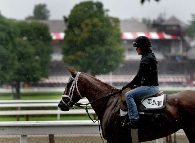 Exercise rider returns to the barn as she endures heavy rainfall after exercising her horse from the trainer Todd Pletcher's training stable  Wednesday morning, Aug. 13, 2014, at  Saratoga Race Course in Saratoga Springs, N.Y. (Skip Dickstein/Times Union) Photo: SKIP DICKSTEIN
