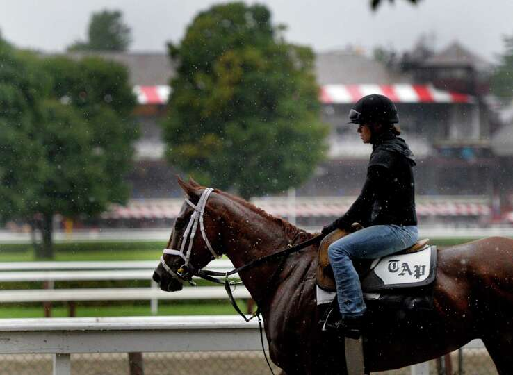 Exercise rider returns to the barn as she endures heavy rainfall after exercising her horse from the