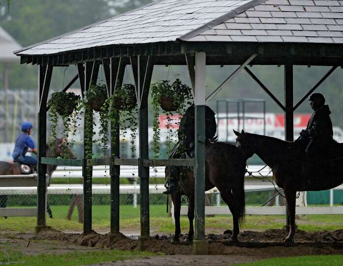 Riders take cover from the heavy rainfall as horses continue to workout  Wednesday morning, Aug. 13,