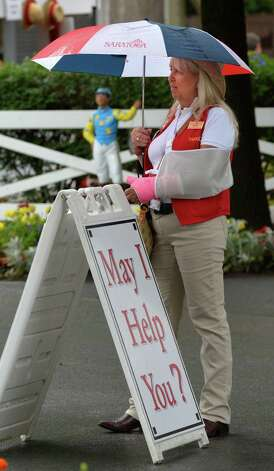 Customer service person, Margie Boucher may be the one that needs help with her arm in a sling and trying to hold an umbrella Wednesday afternoon, Aug. 13, 2014, at Saratoga Race Course in Saratoga Springs, N.Y.    (Skip Dickstein/Times Union) Photo: SKIP DICKSTEIN