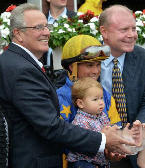Troy Mayor Lou Rosamilia, left presents the winner's trophy to jockey Javier Castellano, center and