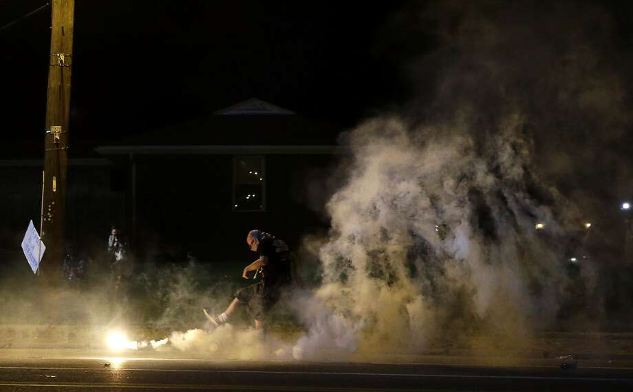 A protester kicks a smoke grenade deployed by police back in the direction of police, Wednesday, Aug. 13, 2014, in Ferguson, Mo. Protests in the St. Louis suburb rocked by racial unrest since a white police officer shot an unarmed black teenager to death turned violent Wednesday night, with people lobbing Molotov cocktails at police who responded with smoke bombs and tear gas to disperse the crowd. (AP Photo/Jeff Roberson) Photo: Jeff Roberson, Associated Press