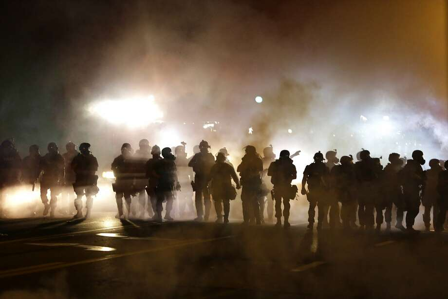 Police advance through smoke during protests Wednesday. Demonstrations have rocked the St. Louis suburb since a white police officer shot unarmed black teenager Michael Brown to death on Saturday. Photo: Jeff Roberson, Associated Press