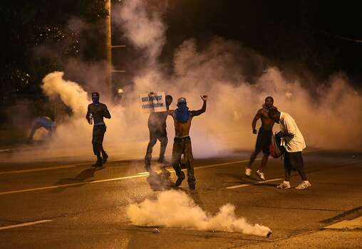 Protesters retreat as tear gas canisters detonate around them on Wednesday, Aug. 13, 2014, in Ferguson, Mo. It was the fourth night of unrest in Ferguson after the fatal police shooting of a teen on Saturday. Photo: Chris Lee, McClatchy-Tribune News Service