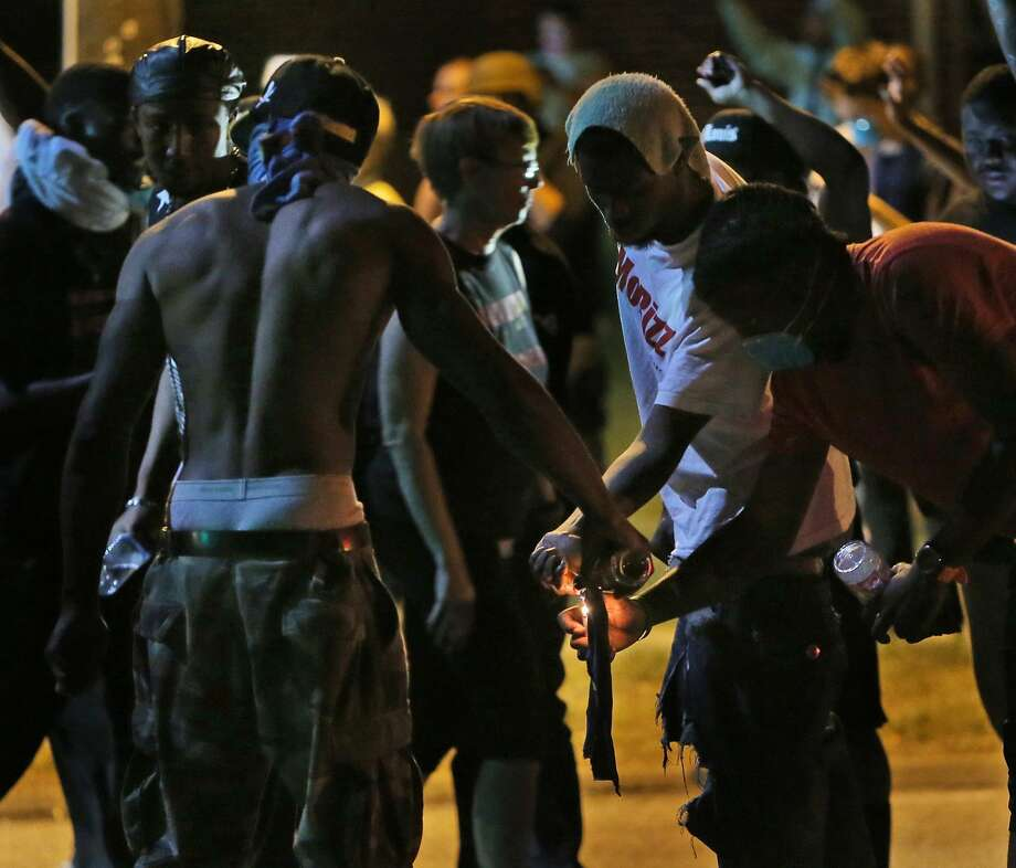 Protesters try unsuccessfully to light a Molotov cocktail as the police prepare to advance on Wednesday, Aug. 13, 2014, in Ferguson, Mo. It was the fourth night of unrest in Ferguson after the fatal police shooting of a teen on Saturday. Photo: Chris Lee, McClatchy-Tribune News Service