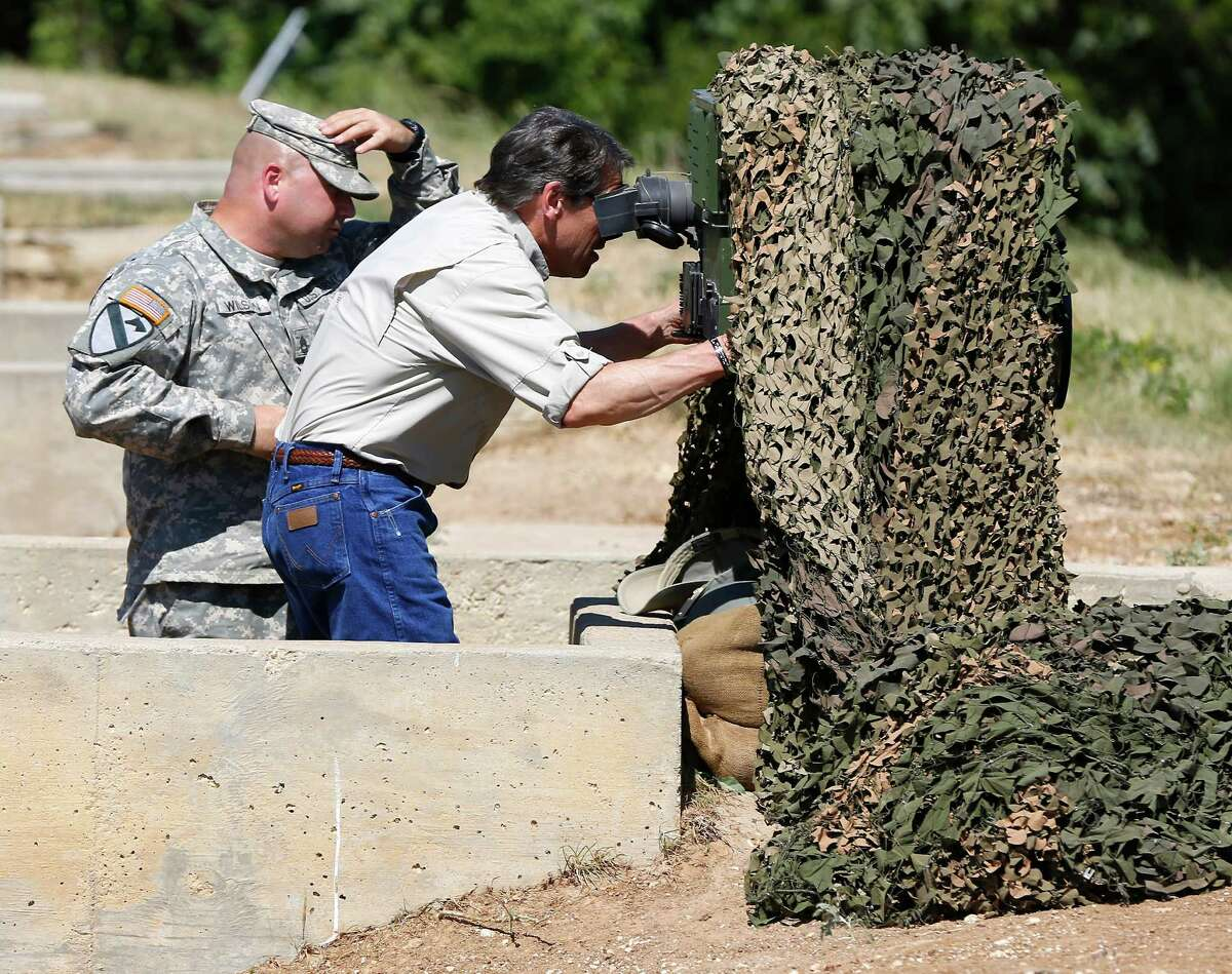 Texas Gov. Rick Perry examines an advanced optics system Wednesday Aug. 13, 2014 at Camp Swift near Bastrop that could be used by Guard troops when they deploy to the border.