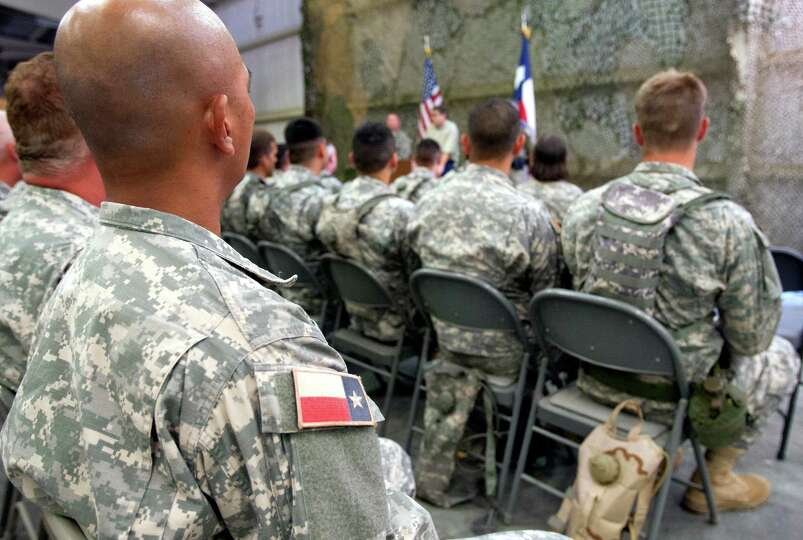 Texas State Guard troops listen to Gov. Rick Perry Wednesday Aug. 13, 2014 as he talks to troops tra
