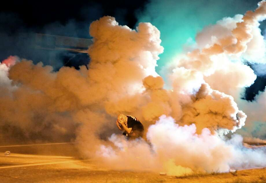 Billowing smoke surrounds a protester in Ferguson, Mo., after police fired smoke bombs and tear gas. Photo: David Carson, Associated Press