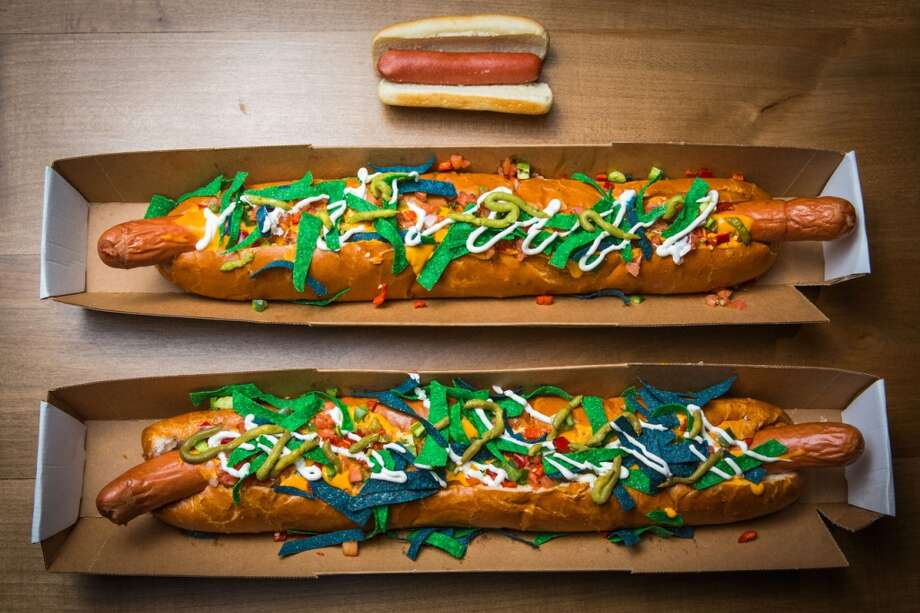 A pair of Colossal Hawk Dogs are shown next to a standard-sized frankfurter at CenturyLink Field. The 24-inch dog is topped with chipotle cheese sauce, pico de gallo, diced red peppers, jalapenos, sour cream, guacamole and tortilla chips. Photo: Joshua Trujillo, Seattlepi.com