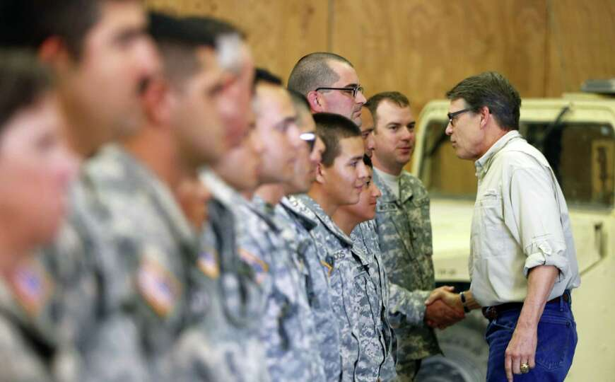 Texas Gov. Rick Perry shakes hands Wednesday Aug. 13, 2014 with Guard troops training at Camp Swift