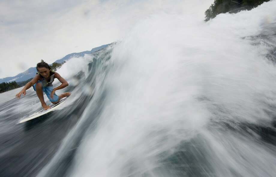 Jordan Smith catches a wave as he wakesurfs on Sproat Lake near Port Alberni, British Columbia, Wednesday, Aug. 13, 2014. (AP Photo/The Canadian Press, Jonathan Hayward) Photo: Jonathan Hayward, Associated Press