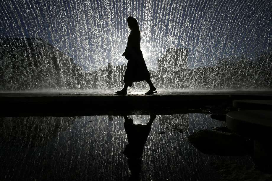 A woman walks under an artificial waterfall outside the Oceanarium of Lisbon, in Portugal, Wednesday, Aug. 13, 2014. (AP Photo/Francisco Seco) Photo: Francisco Seco, Associated Press