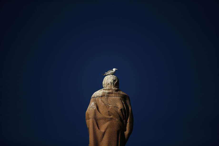 A bird perches on the head of a statue in the harbor of Tarifa, Spain. Judging from the guano, it's 