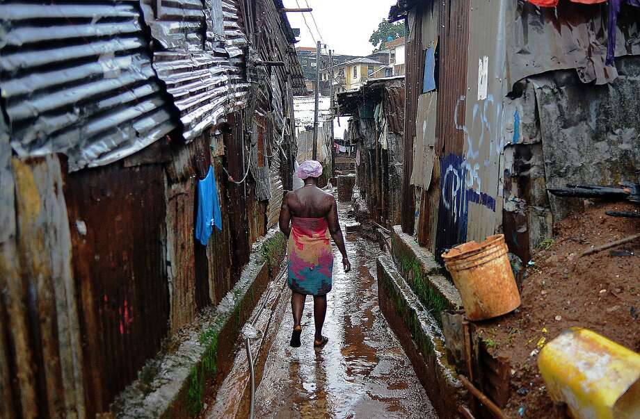 A woman walks through Kroo town slum in Freetown on August 13, 2014. The World Health Organisation (WHO) revealed that the latest death toll from the Ebola virus in Guinea, Sierra Leone, Liberia and Nigeria had claimed more than1000  lives. Health Organisations are looking into the possible use of experimental drugs to combat the latest outbreak in West Africa which is also the largest ebola outbreak in history. AFP PHOTO/Carl de SouzaCARL DE SOUZA/AFP/Getty Images Photo: Carl De Souza, AFP/Getty Images