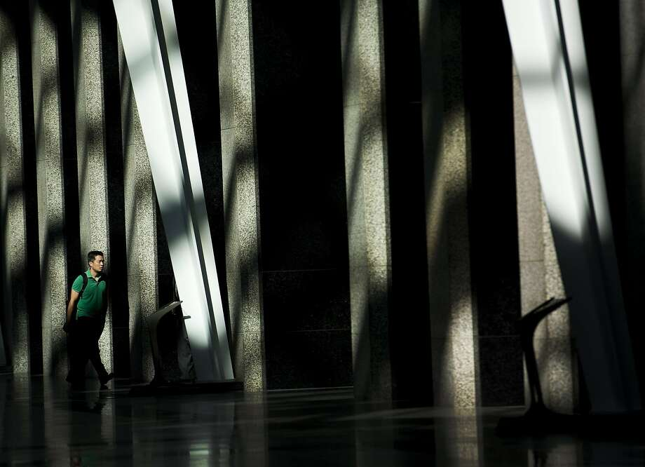 A man makes his way to work though the early morning light at Brookfield Place  in downtown Toronto on Wednesday, Aug. 13, 2014. (AP Photo/The Canadian Press, Nathan Denette Photo: Nathan Denette, Associated Press