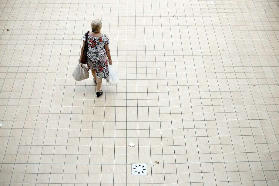 A customer carries her purchases in plastic shopping bags as she walks towards the exit of an indoor market in Rome, Italy, on Tuesday, Aug. 12, 2014. Italy's economy shrank 0.2 percent in the second quarter after contracting 0.1 percent in the previous three months. Photographer: Alessia Pierdomenico/Bloomberg Photo: Alessia Pierdomenico, Bloomberg