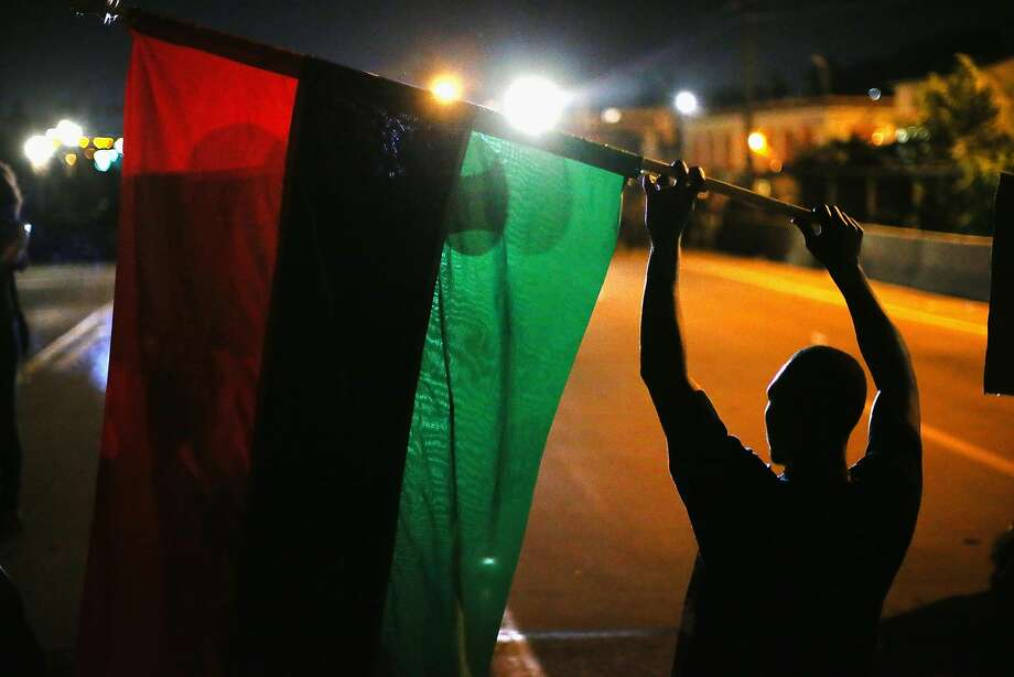 FERGUSON, MO - AUGUST 12:  Demonstrators hold up a Pan-African flag to protest the killing of teenager Michael Brown on August 12, 2014 in Ferguson, Missouri. Brown was shot and killed by a police officer on Saturday in the St. Louis suburb of Ferguson. Ferguson has experienced two days of violent protests since the killing but, tonight's protest was peaceful.  (Photo by Scott Olson/Getty Images) Photo: Scott Olson, Getty Images