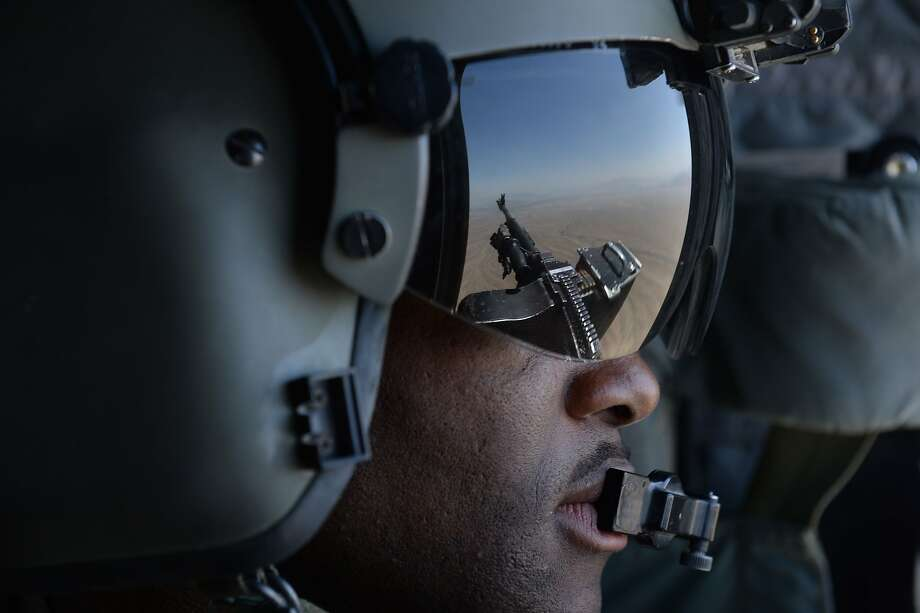 This photo taken on august 11, 2014 shows a US soldier, part of the NATO-led International Security Assistance Force (ISAF), manning a machine gun onboard a Chinook helicopter over the Gardez district of Paktia province.  All NATO combat troops will be out of Afghanistan by the end of the year, though some US special forces are set to stay on to conduct discreet strikes against Al-Qaeda remanents.      AFP PHOTO / SHAH MaraiSHAH MARAI/AFP/Getty Images Photo: Shah Marai, AFP/Getty Images