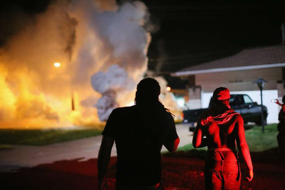 Demonstrators, protesting the shooting death of teenager Michael Brown, scramble for cover as police fire tear gas on August 13, 2014 in Ferguson, Missouri. Brown was shot and killed by a Ferguson police officer on Saturday. Ferguson, a St. Louis suburb, is experiencing its fourth day of violent protests since the killing. Photo: Scott Olson, Getty Images