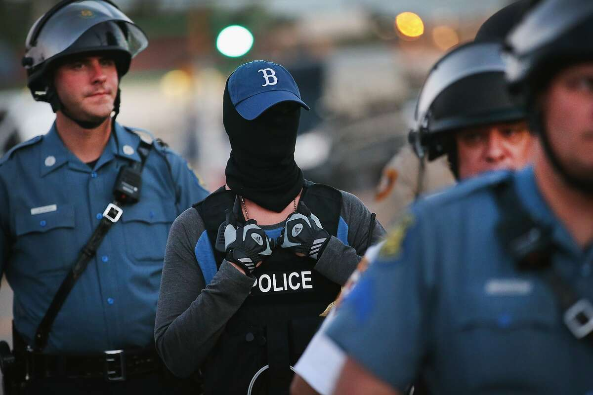 A police officer standing watch as demonstrators protest the shooting death of teenager Michael Brown conceals his/her identity on August 13, 2014 in Ferguson, Missouri. Brown was shot and killed by a Ferguson police officer on Saturday. Ferguson, a St. Louis suburb, is experiencing its fourth day of violent protests since the killing.