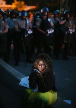 A demonstrator protesting the shooting death of teenager Michael Brown looks at her phone as police keep watch nearby on August 13, 2014 in Ferguson, Missouri. Brown was shot and killed by a Ferguson police officer on Saturday. Ferguson, a St. Louis suburb, is experiencing its fourth day of violent protests since the killing. Photo: Scott Olson, Getty Images
