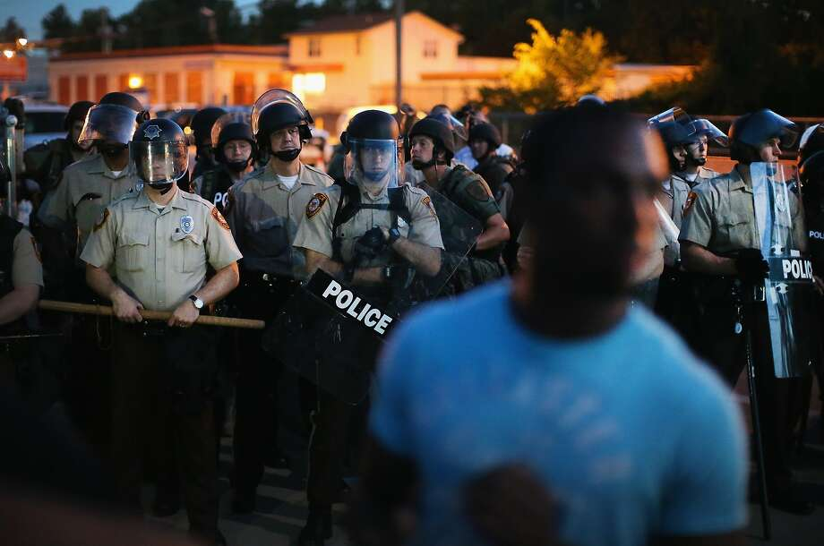 Police stand watch as demonstrators protest the shooting death of teenager Michael Brown on August 13, 2014 in Ferguson, Missouri. Brown was shot and killed by a Ferguson police officer on Saturday. Ferguson, a St. Louis suburb, is experiencing its fourth day of violent protests since the killing. Photo: Scott Olson, Getty Images