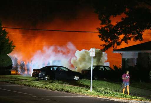 A young woman walks from a corner after police standing near the corner fired tear gas at her on August 13, 2014 in Ferguson, Missouri. Ferguson is experiencing its fourth day of unrest after following the shooting death of teenager Michael Brown on Saturday. Brown, who was not armed was shot and killed by a Ferguson police officer. Photo: Scott Olson, Getty Images