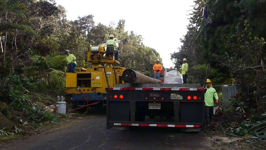 More than 6,000 Puna residents are waiting for power to be restored while HELCO workers clear debris, remove downed power lines and replace utility poles in the rural area. Photo: HELCO