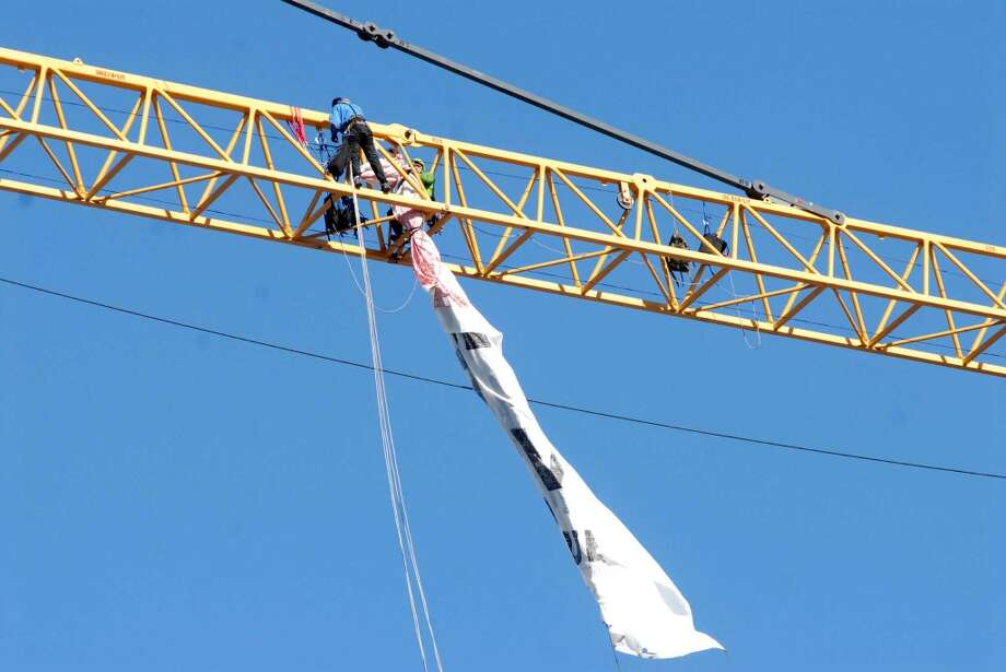 Protestors outside 66 Summer Street in Stamford, Conn. have climbed a crane and unfurled a banner protesting UBS and its mountaintop mining practices on Monday November 25, 2013. Photo: Dru Nadler