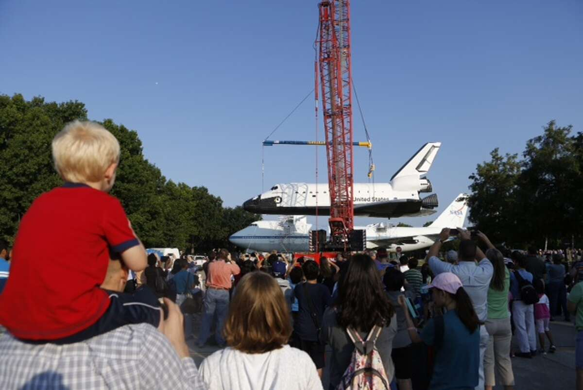 Crews get ready to place the space shuttle replica on top of the real transport plane early Thursday morning, Aug. 14, 2014, outside Johnson Space Center in Houston.
