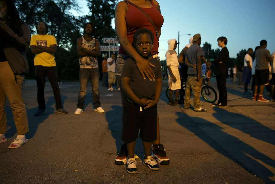Jeremiah Parker, 4, stands in front of his mother, Shatara Parker, as they attend a protest Wednesday, Aug. 13, 2014, in Ferguson, Mo. Nights of unrest have vied with calls for calm in a St. Louis suburb where Michael Brown, an unarmed black teenager was killed by police, while the community is still pressing for answers about the weekend shooting. Photo: Jeff Roberson, Associated Press