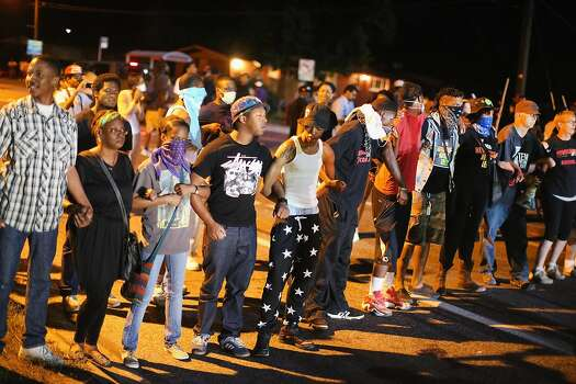 Demonstrators protest the shooting death of teenager Michael Brown on August 13, 2014 in Ferguson, Missouri. Brown was shot and killed by a Ferguson police officer on Saturday. Ferguson, a St. Louis suburb, is experiencing its fourth day of violent protests since the killing.  Photo: Scott Olson, Getty Images