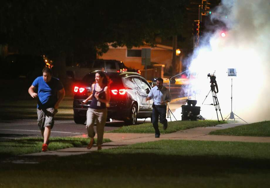 An Al Jazeera television crew, covering demonstrators protesting the shooting death of teenager Michael Brown, scramble for cover as police fire tear gas into their reporting position on August 13, 2014 in Ferguson, Missouri. Brown was shot and killed by a Ferguson police officer on Saturday. Ferguson, a St. Louis suburb, is experiencing its fourth day of violent protests since the killing.  Photo: Scott Olson, Getty Images