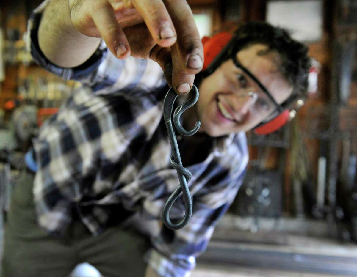 Nick Moreau shows off a hook that he has just crafted in his metal shop Tuesday, August 12, 2014. Nicholas Wicks Moreau, 26, of Westport, Conn., an artist blacksmith, uses his grandfather's old blacksmith shop in the garage of his family's Danbury home to do his work.