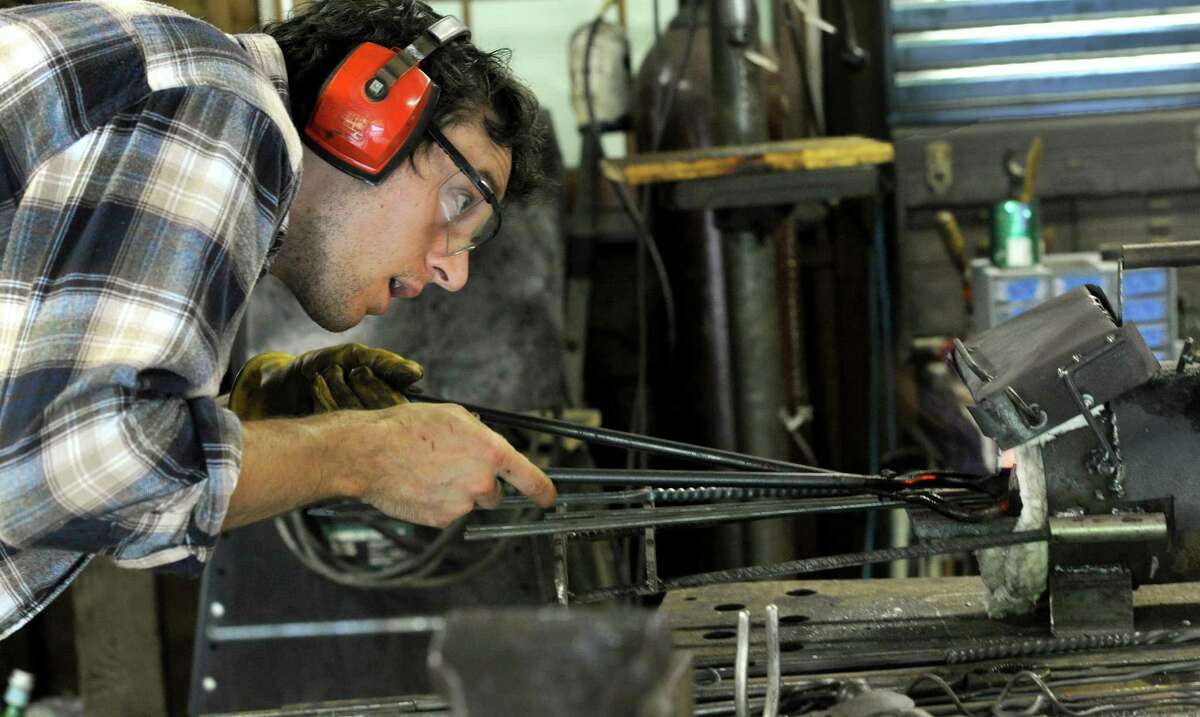 Nick Moreau keeps an eye on the irons as they heat up in the fire of the forge. Nicholas Wicks Moreau, 26, of Trumbull, Conn., an artist blacksmith, uses his grandfather's old blacksmith shop in the garage of his family's Danbury home to do his work.