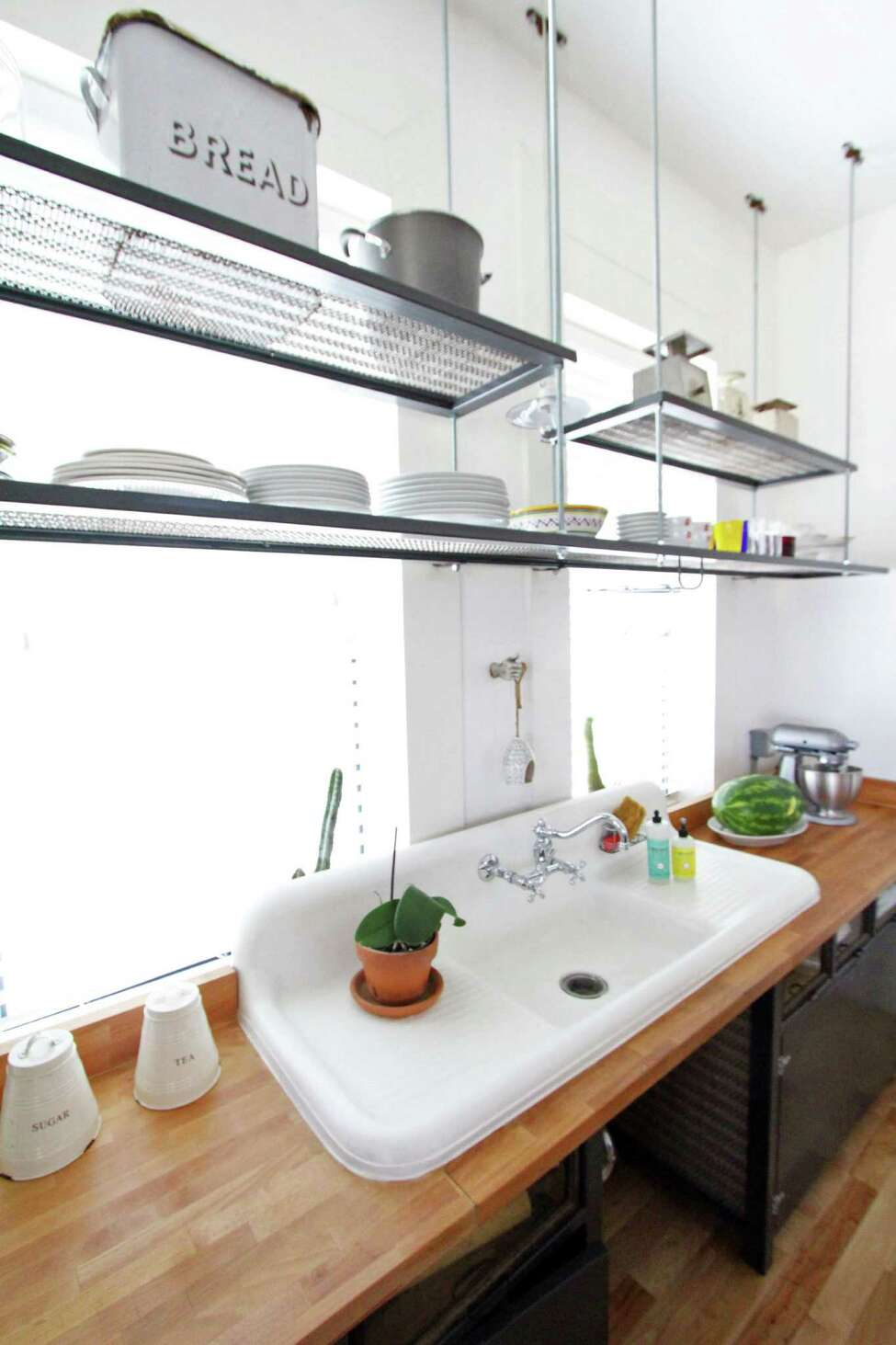 Suspended metal shelves hang above the double drainboard sink, which Vincent Valdez and Adriana Corral bought at Architectural Antiques.